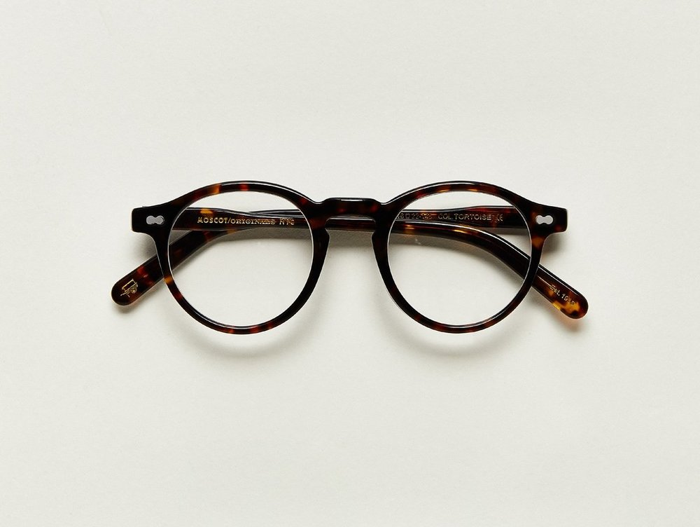 MOSCOT - Militzen Opticals    £245    COLOUR  Tortoise   SIZE  46  The round, full-vue MILTZEN, first introduced in the 1930s, is eponymously named for our Uncle Heshy, who inexplicably everyone called Uncle Miltzen. And it stuck. So there you go, world... The MILTZEN.  Handcrafted using Italian acetate  Features adjoined dot rivets  Comfortable key hole nose bridge  Includes acetate nose pads  3-Barrel hinge  MOSCOT temple engravings