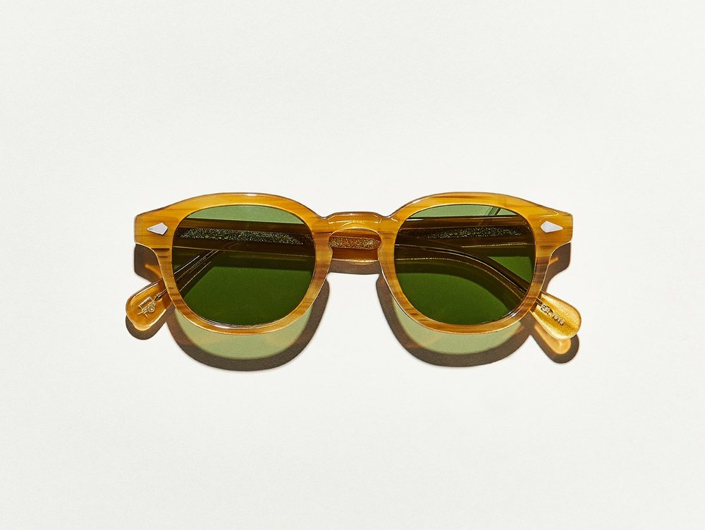 MOSCOT - Lemtosh Sunglasses   £265   COLOUR  Blonde   SIZE  46  This rounder number has served as the calling card for generations of creative, thoughtful, free-spirited intellectuals and artistes – from James Dean to Johnny Depp.  Handcrafted using Italian acetate featuring unique patterns distinctive to each frame  Features diamond rivets  Features real glass lenses in Calibar Green