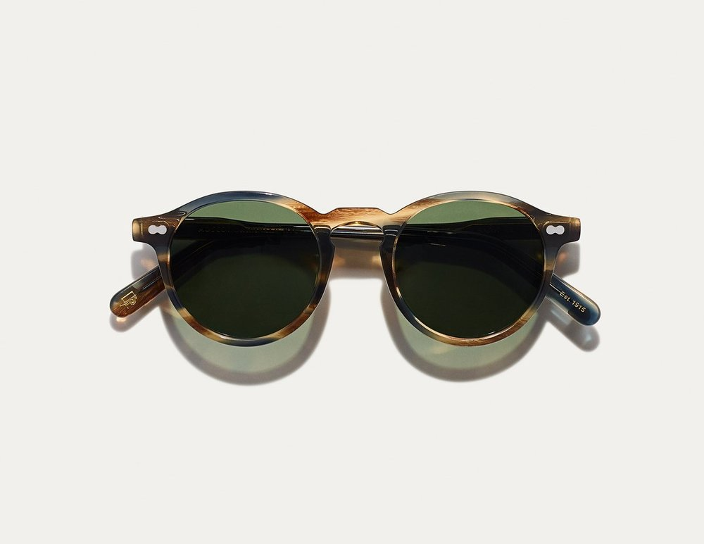 MOSCOT - Militzen Sunglasses   £265   COLOUR  Bark   SIZE  46  The round, full-vue MILTZEN, first introduced in the 1930s, is eponymously named for our Uncle Heshy, who inexplicably everyone called Uncle Miltzen. And it stuck. So there you go, world... The MILTZEN.    Handcrafted using Italian acetate featuring unique patterns distinctive to each frame  Features two adjoined dot rivets  Includes acetate nose pads  3-Barrel hinge  Features real glass lenses in G-15