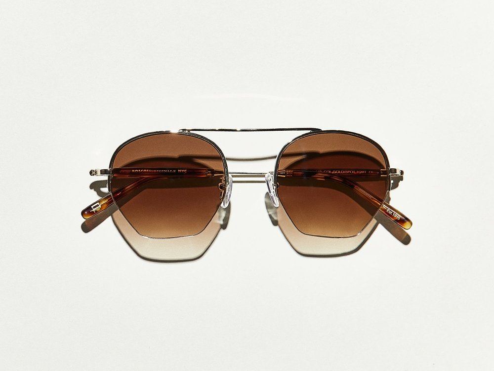 "MOSCOT - Punim SE Sunglasses  £285   COLOUR  Gold/Spot Tortoise   SIZE  49  ""Look at that Punim"" was a phrase heard all too often upon entering Grandma Sylvia's house for family gatherings. No matter the occasion, cheeks were pinched and kisses were had. For that sentiment alone, we present The PUNIM, new for SS18. Many years later, we can only imagine the expressions the gang would have said with this latest Classiconic launch.    Handcrafted using a combination of metal and Italian acetate featuring unique patterns distinctive to each frame  Features semi-rimless metal front  Comfortable elevated nose bridge  Signature acetate tips   Features ZEISS nylon lenses with Brown Gradient"