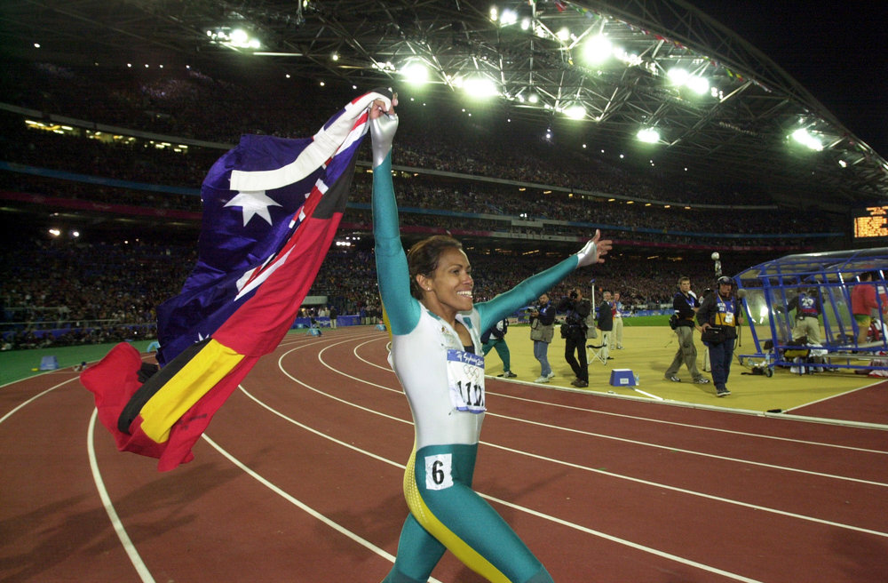Cathy Freeman walks a lap of honour, carrying the Australian and Aboriginal Flags, after winning Gold in the Women's 400m Finals. (AAP PHOTO/Dean Lewins).