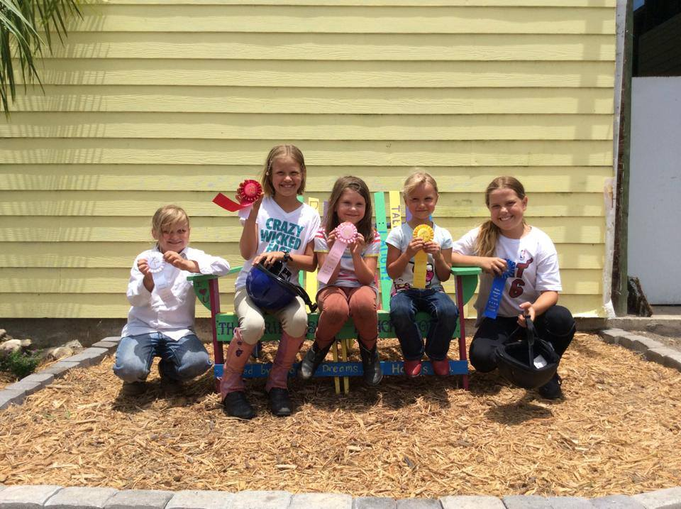 The girls showing off their ribbons on the friendship bench. Everyone is a winner at our farm!