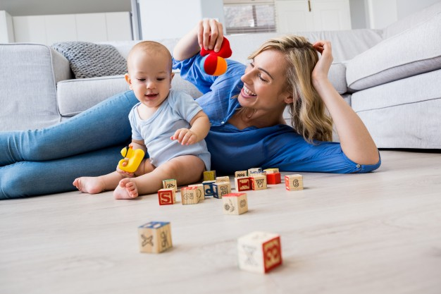 mother-looking-at-baby-boy-playing-with-toys-in-living-room_1170-428 (1).jpg