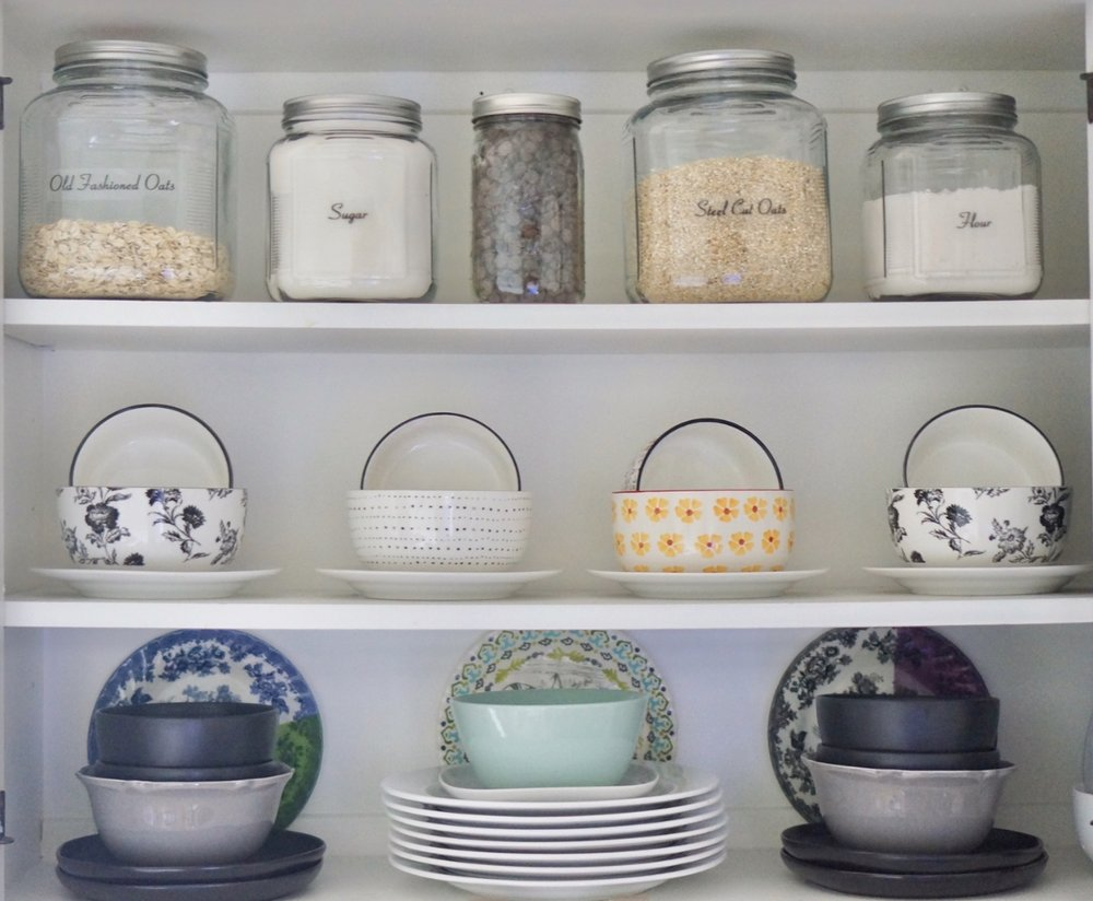 open shelving with glass jars and a display of dishware