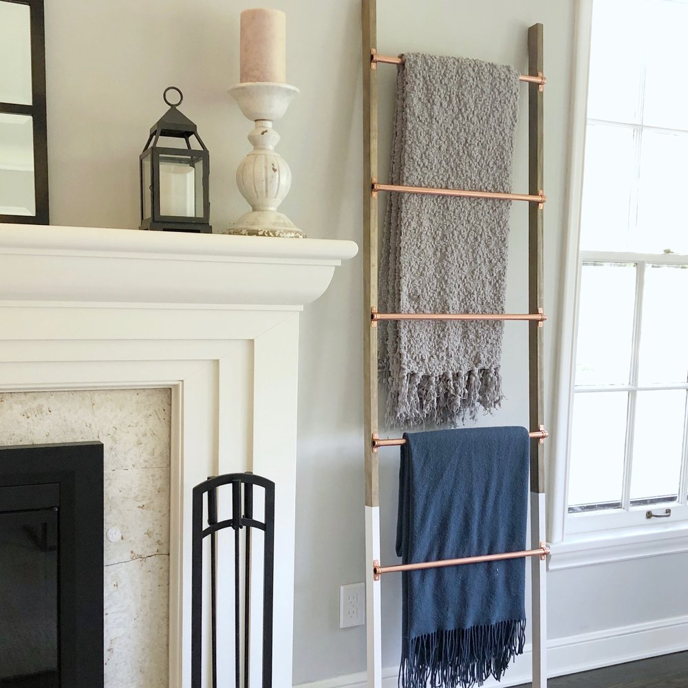 blanket ladder by a fireplace