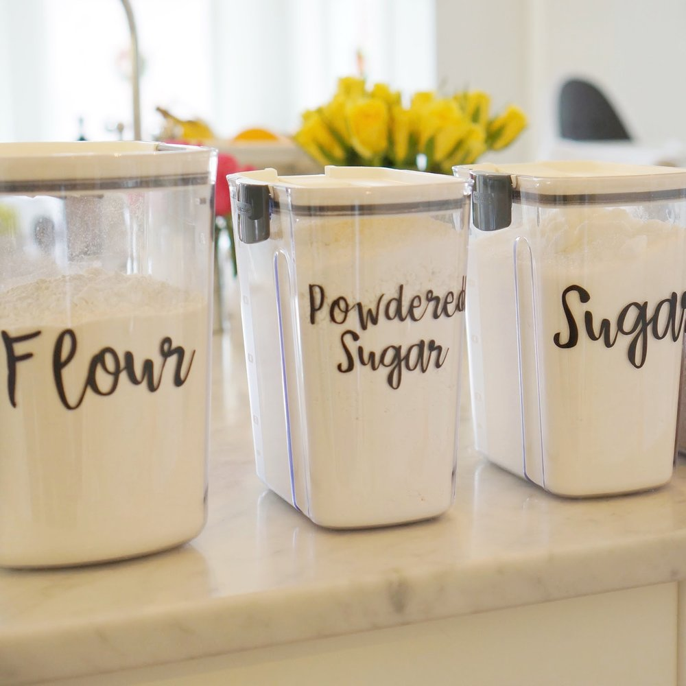 flour, sugar, and powdered sugar baking containers with labels.
