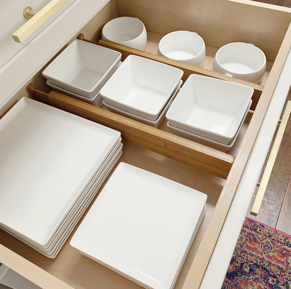 White dishes organized in a drawer with dividers