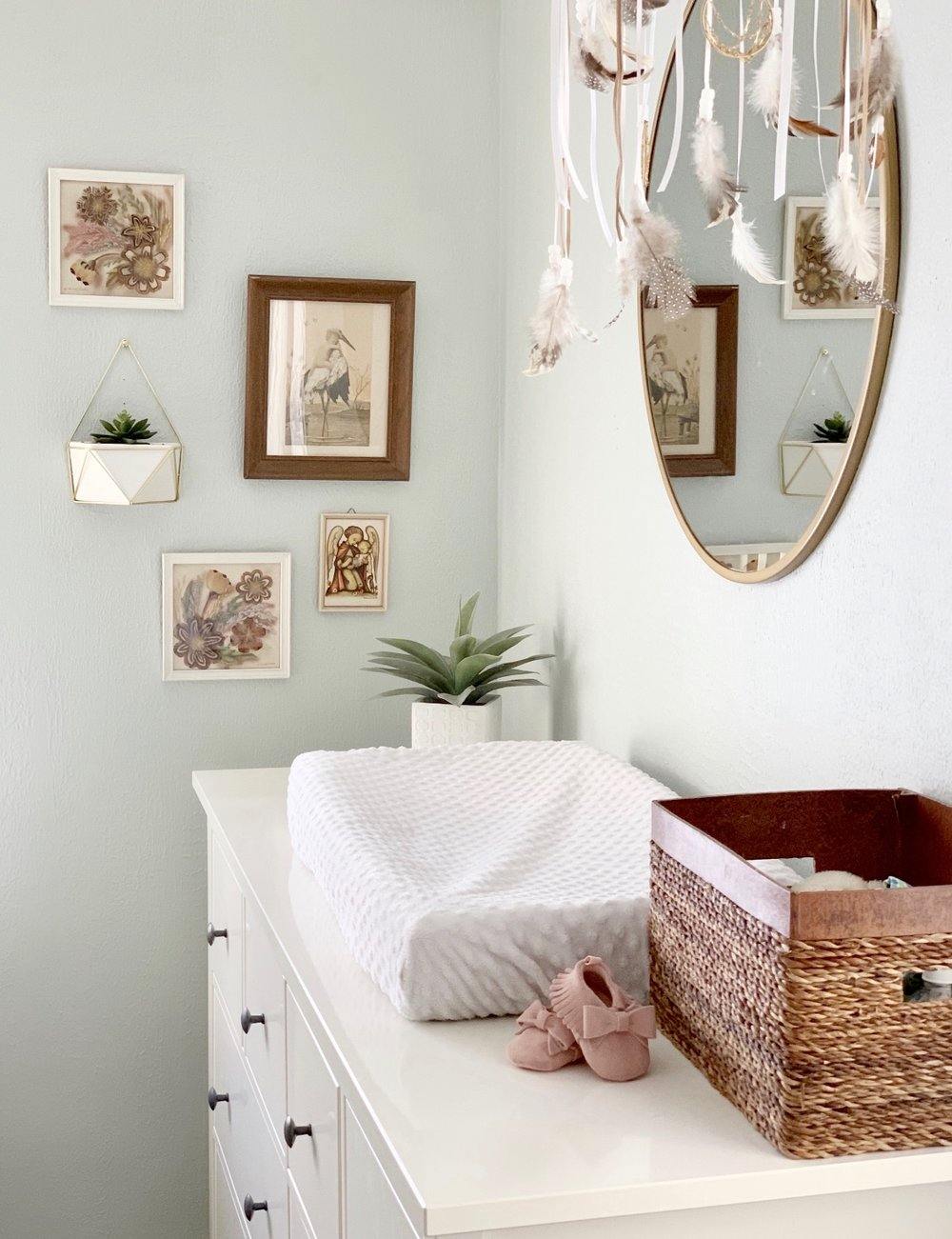Gallery wall in girls nursery.  changing table with round mirror on dresser