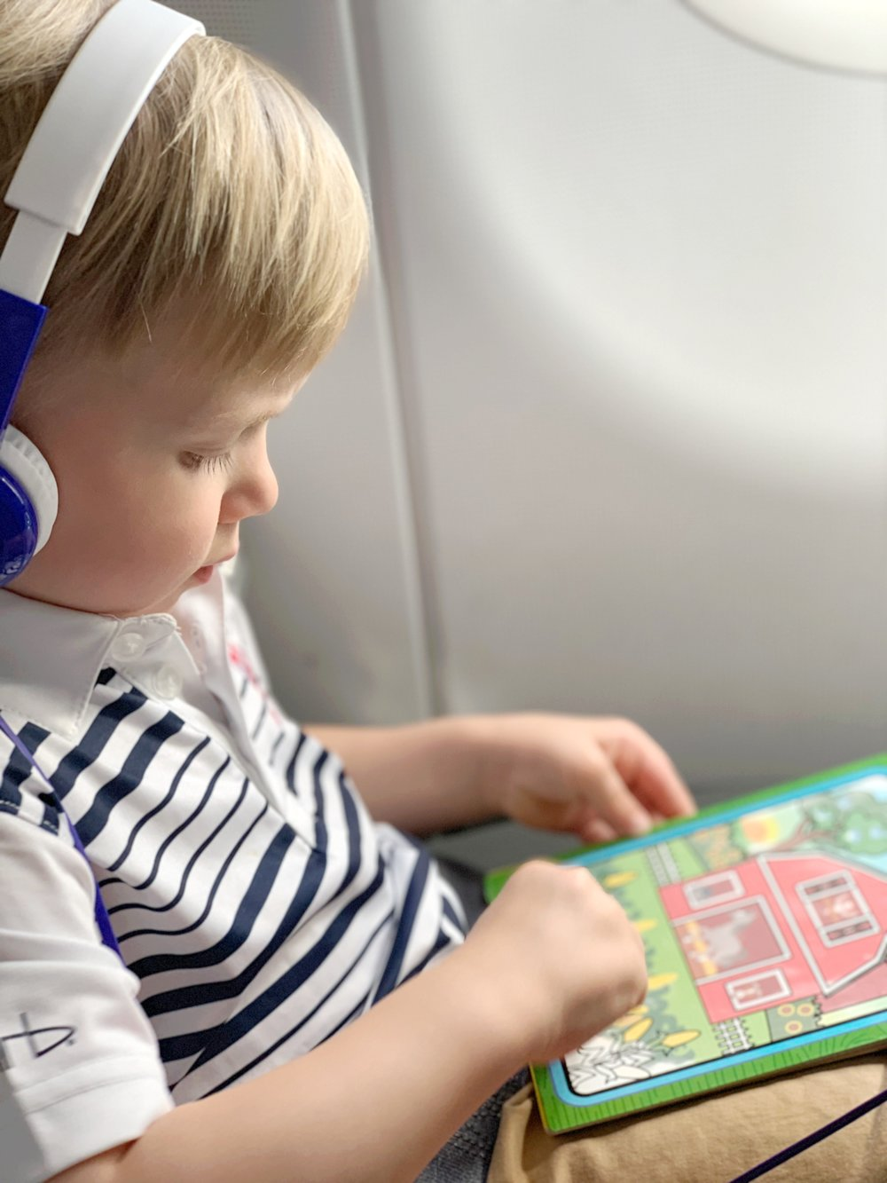 little boy with headphones on coloring on an airplane