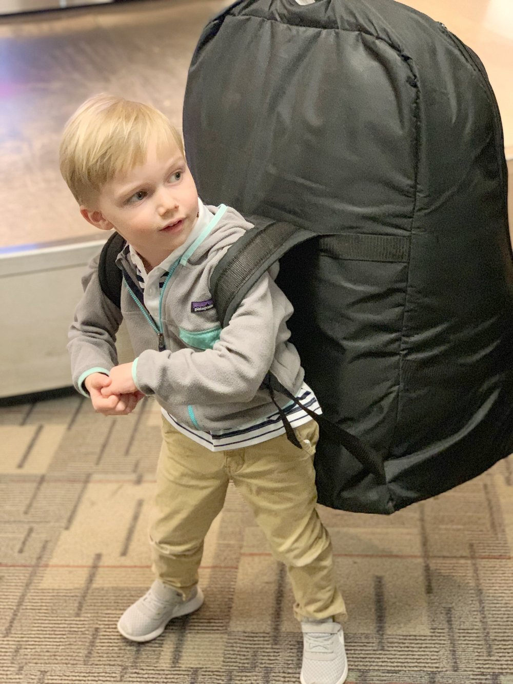 Little boy pretending to carry a car seat travel backpack