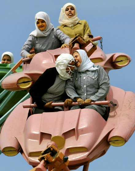 Palestinian schoolgirls enjoy a ride at an amusement park outside Gaza City, March 26, 2006.