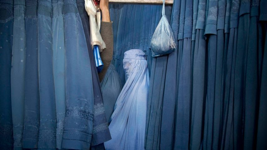 Woman tries on a burka in Kabul's old city, April 2013.