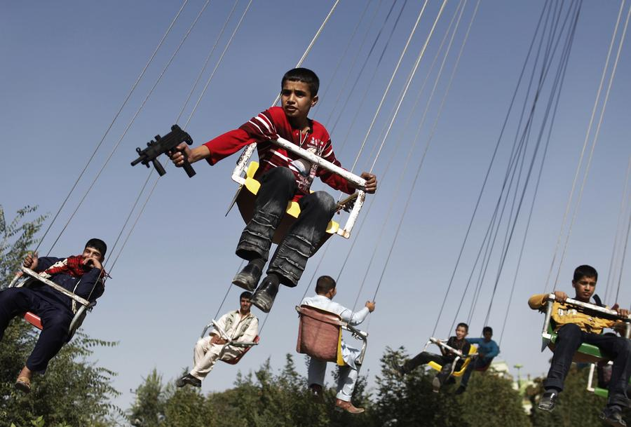An Afghan boy holds a toy gun as he enjoys a ride with others on a merry-go-round to celebrate the Eid al-Fitr festival in Kabul, September 20, 2009.