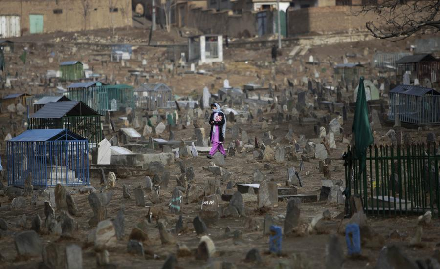 An Afghan girl crosses a cemetary in the outskirts of Kabul, November 25, 2009.