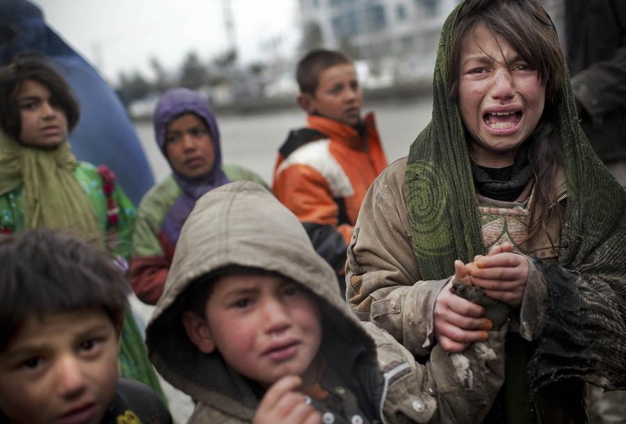 An Afghan refugee girl reacts after another child stole her food voucher while she was queuing in front a truck organized by the World Food Program in Kabul, March 4, 2012.