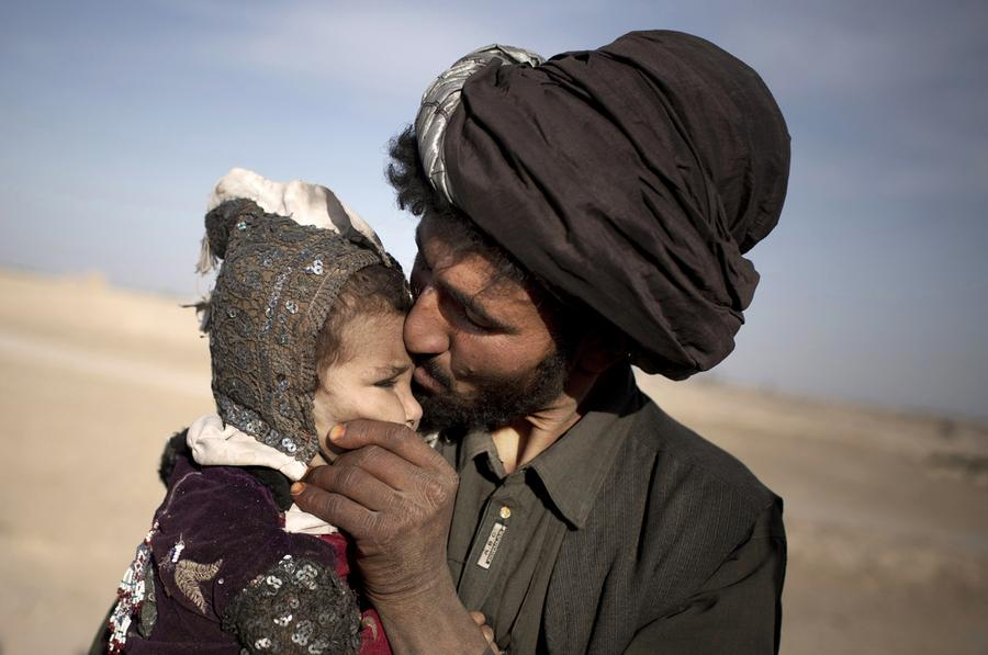 An Afghan nomad kisses his young daughter while watching his herd in Marjah, Helmand province, October 20, 2012.