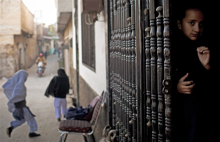 A young girl peeks out from the barred entrance to the Khushal School for Girls in Mingora, Swat Valley, November 15, 2012.