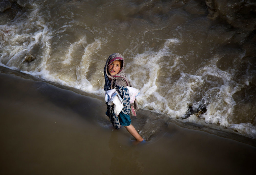 An Afghan girl takes a short cut through a streaming river on the outskirts of Kabul, Afghanistan, May 15, 2013.