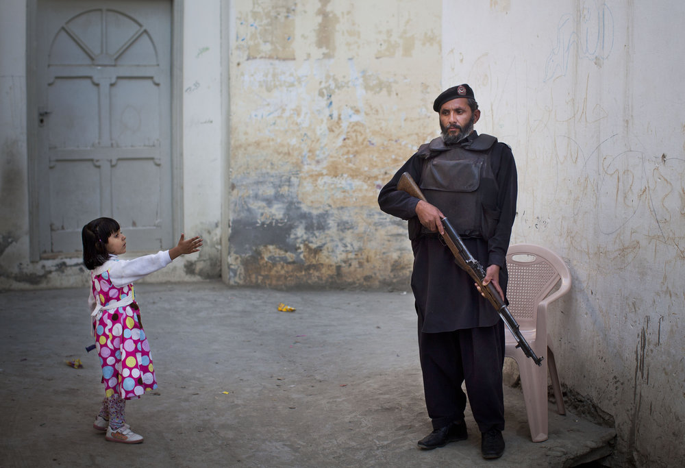 A young girl reaches out to a Pakistani policeman in Mingora, Swat Valley, Pakistan. November 15, 2012.