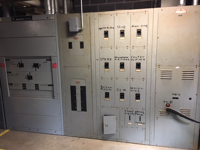 The original 1956 electrical panels still exist juxtaposed next to new ones from 1994. Maintenance staff do not touch the 1956 switches; they would break and risk cutting off power to the original section of the high school.
