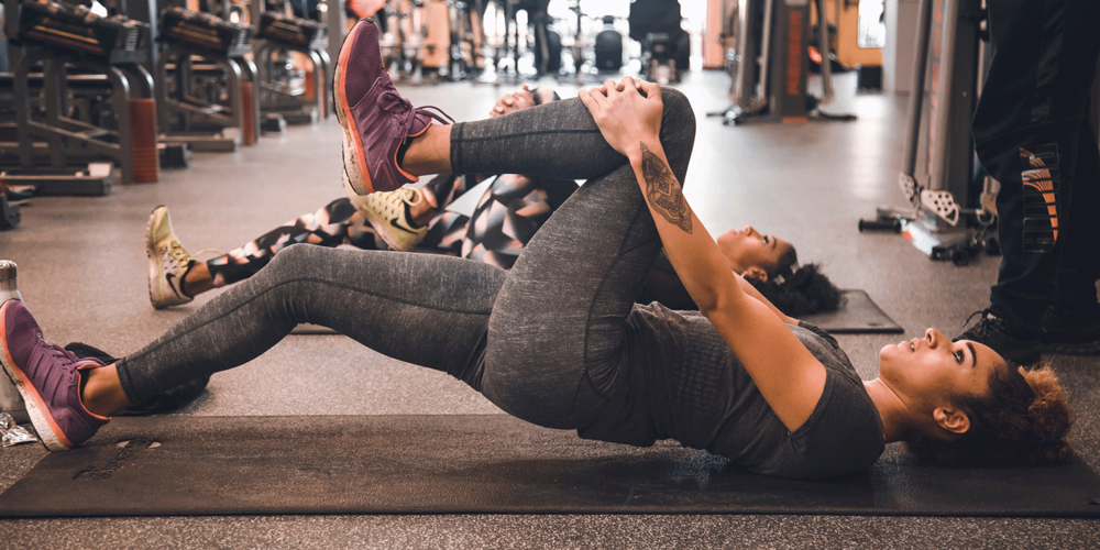 Two women at the gym stretching and training - these are more people who would use Shower in a Can after exercise when on the move.