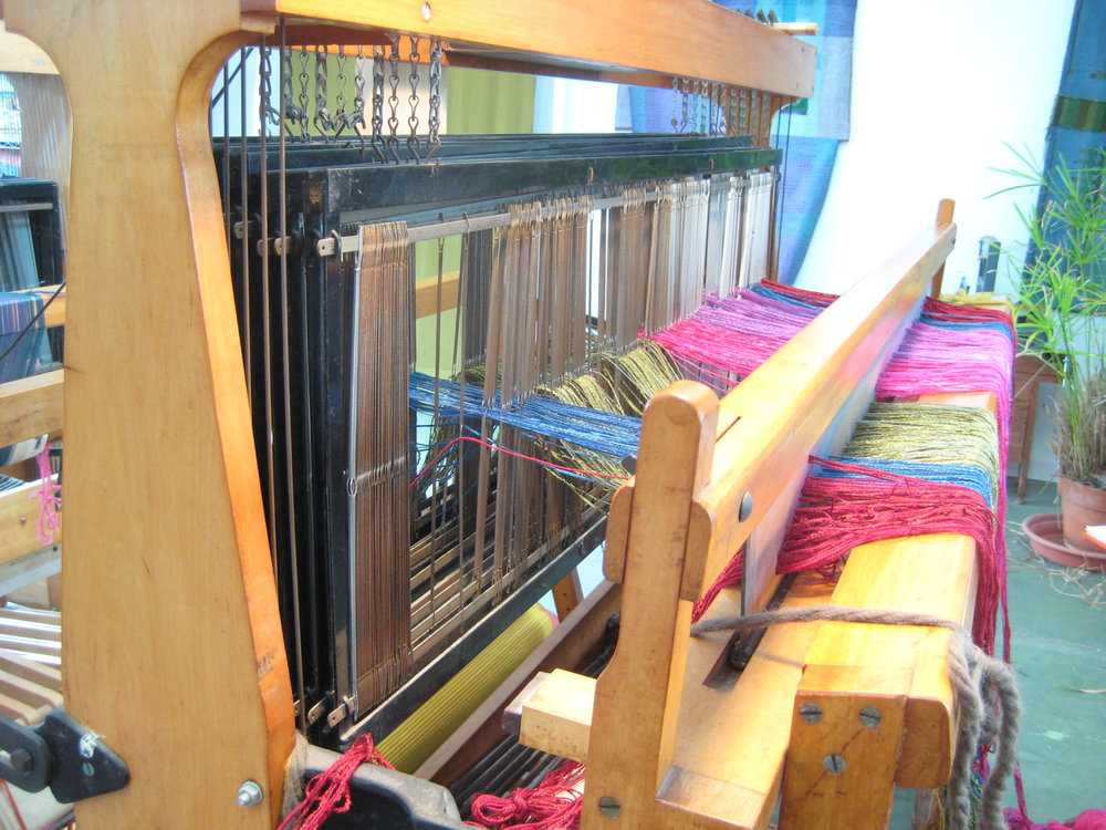 After the reed is threaded, the threads go through heddles on harnesses or shafts in the correct sequence of the pattern to be woven. Shown here, I am threading a Summer & Winter pattern on 10 harnesses.