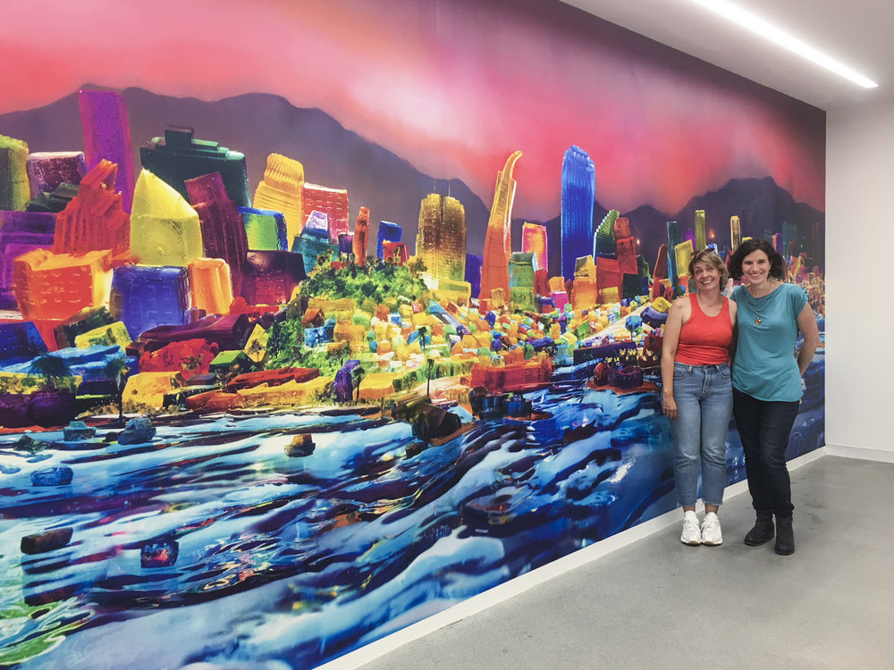 "Kristin Farr and Liz Hickok with her installation of her mural ""View From Alcatraz"" from the ""San Francisco in Jell-O"" series."