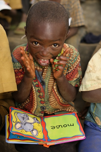 A child in Rwanda enjoys a book donated through LuDela's  Better Light, Better Lives  mission.