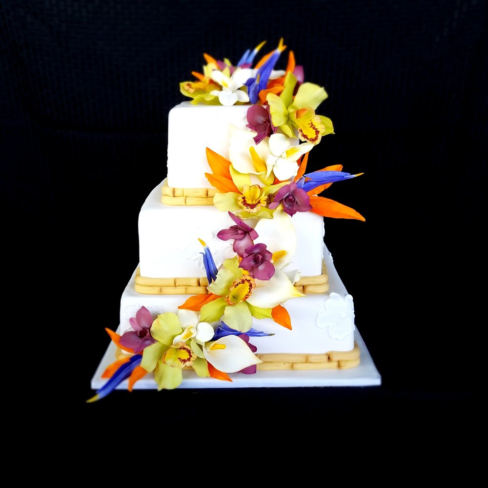 three tier square white rolled fondant wedding cake with cascade of sugar orchids, bird of paradise and calla lilies Hilo Hawaii Big Island Kailua-Kona