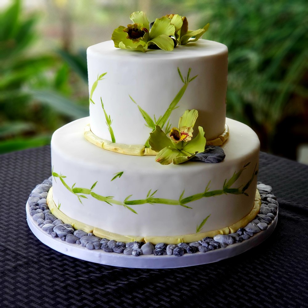 Two tier round white hand painted rolled fondant wedding cake with sugar orchids and pebbles Hilo Hawaii Big Island Kailua Kona