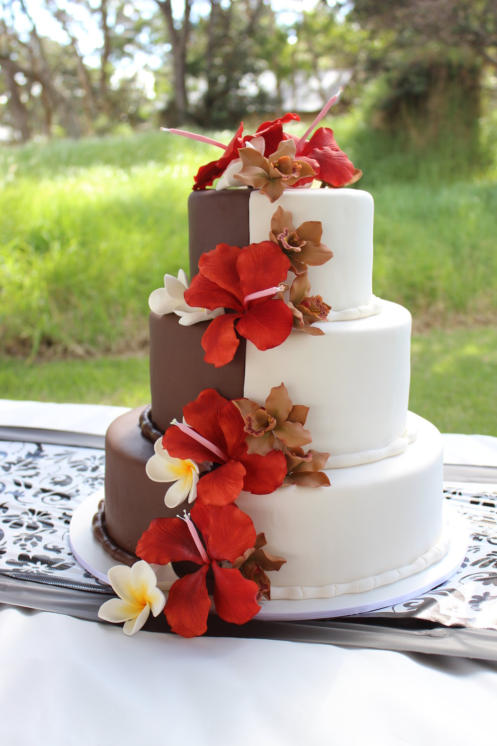 Three tier round white and chocolate rolled fondant wedding cake with sugar orchid and hibiscus cascade Hilo Hawaii Big Island Kailua-Kona