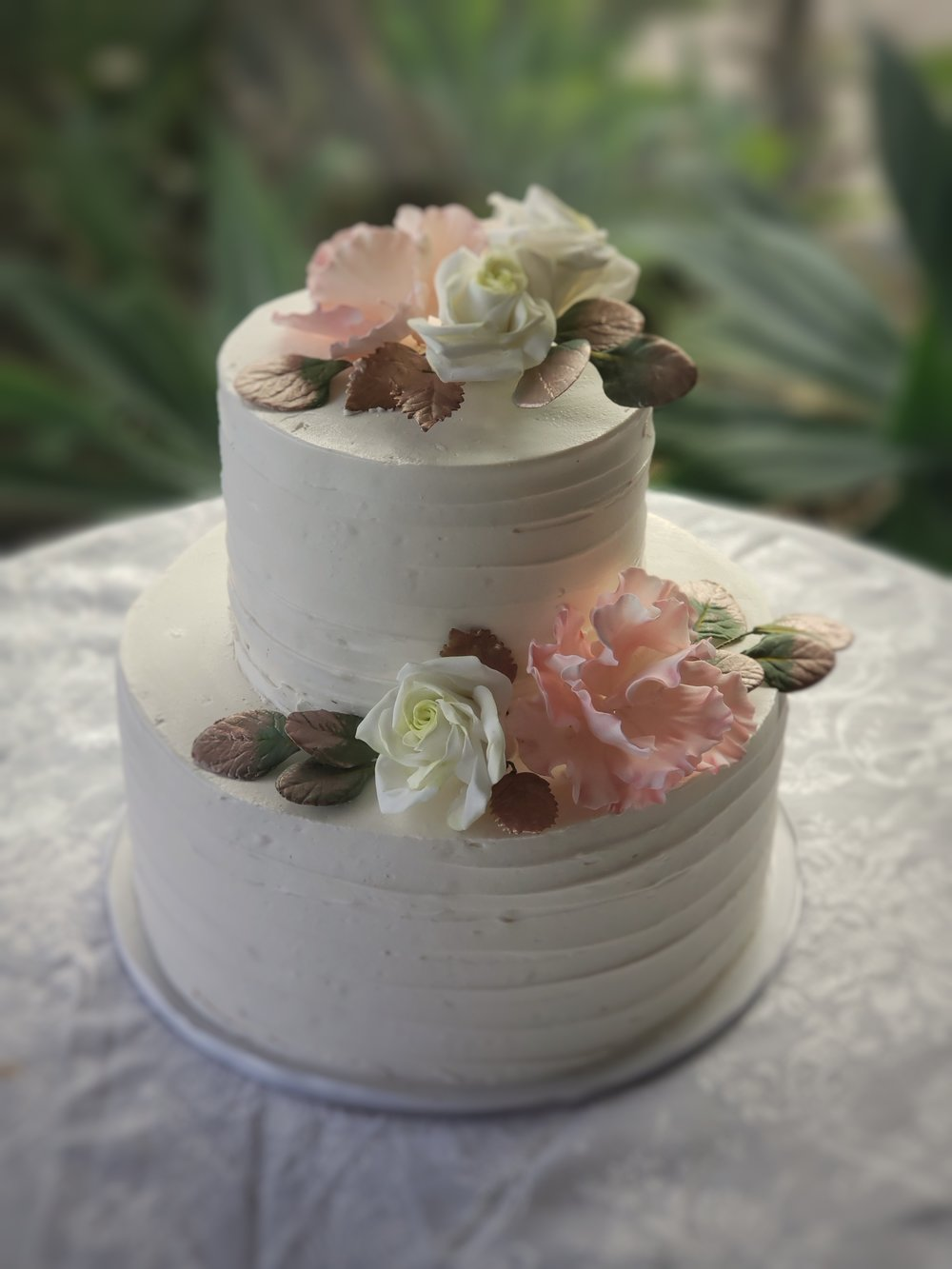 Two tier round textured buttercream wedding cakewith sugar peonies, roses and rose gold leaves Hilo Hawaii Big Island Kailua-Kona