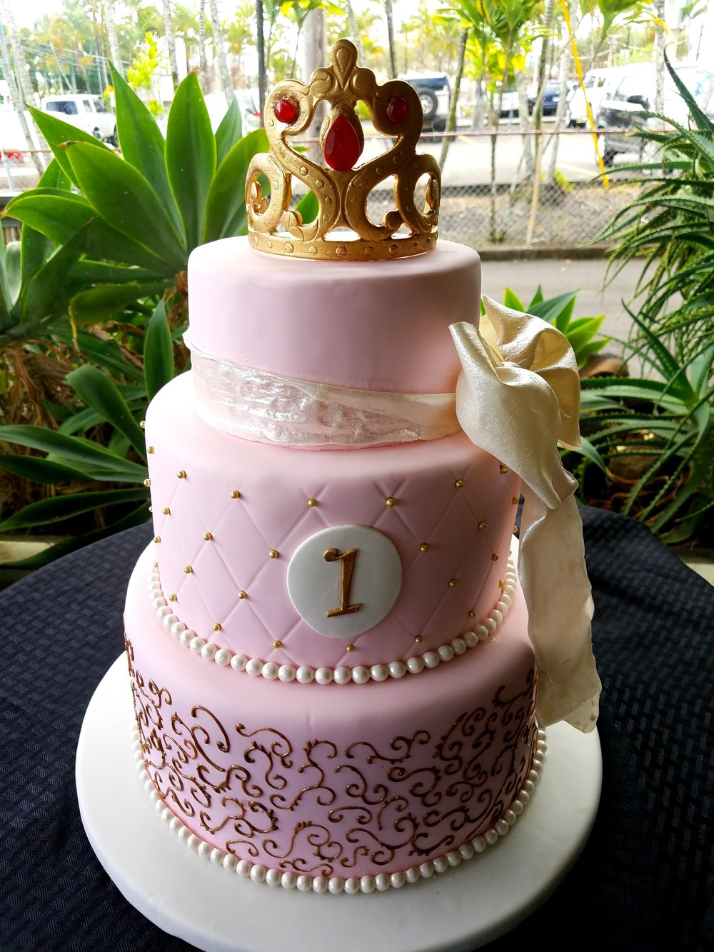 Three tier pink rolled fondant princess birthday cake with piped gold scroll work, edible sugar bow and gold sugar crown topper Hilo Hawaii Big Island Kailua-Kona