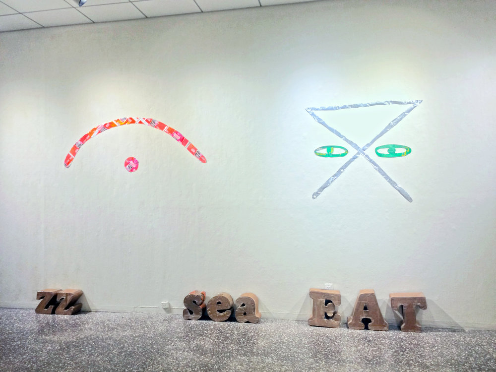 "Wall, left:  Hobo Signs: Cops Active.  Mylar Duncan Donuts Coffee bags, 24 x 48"", 2018. Wall right:  Hobo Signs: Safe Camp.  Mylar Wellness cat and Natures Domain dog food bags, 40 x 40"", 2018. Floor:  In Our Words.  Corrugated cardboard, hot melt glue and biodegradable cellulose packaging tape. 2017-18."