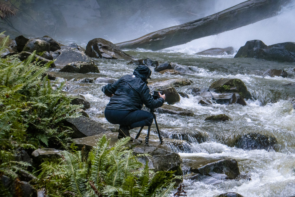 Photographers climb barriers to access the falls to get a closer look and frame up shots setting up compositions on moss covered rocks.