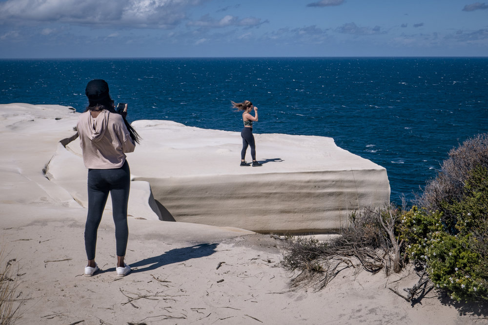 Selfie time, except hesitant at first because of the wind, one of the girls walks out onto the rock for her 15 seconds of InstaFame.