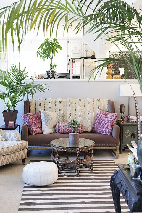 Moroccan poufs and traditional furniture create and eclectic living space. Image via Bohemian Treehouse