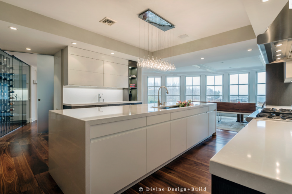 This kitchen features a layered lighting plan with ceiling lights, under-cabinet lighting, and a dramatic statement chandelier.