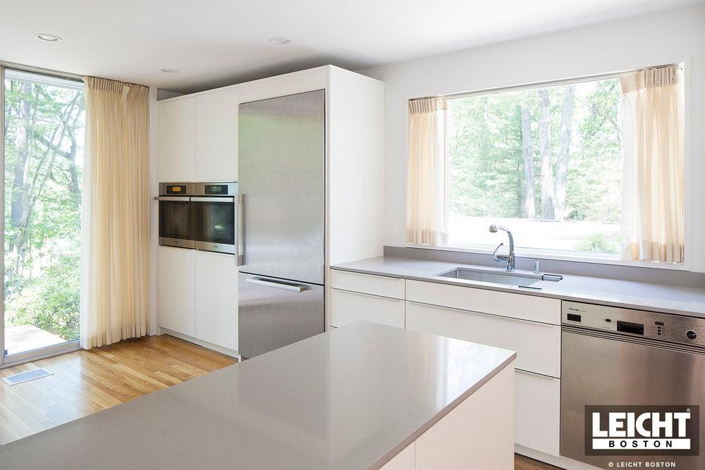 White modern leicht kitchen, granite countertops, and stainless steel appliances