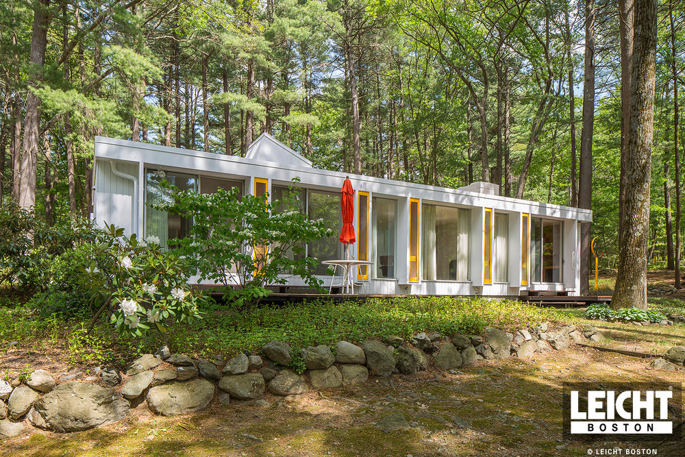 Mid century modern bungalow set in the woods. Floor to ceiling windows. White siding and yellow accents.