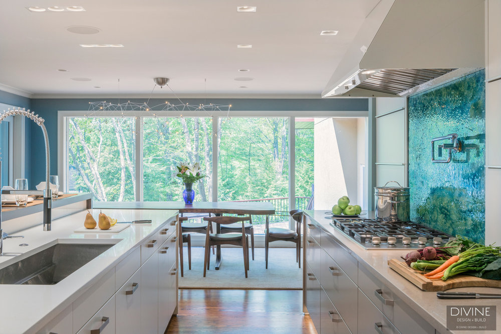 Modern leicht kitchen with white and grey cabinets. Custom blue and green backsplash. Brushed nickel hardware and cambria countertops.