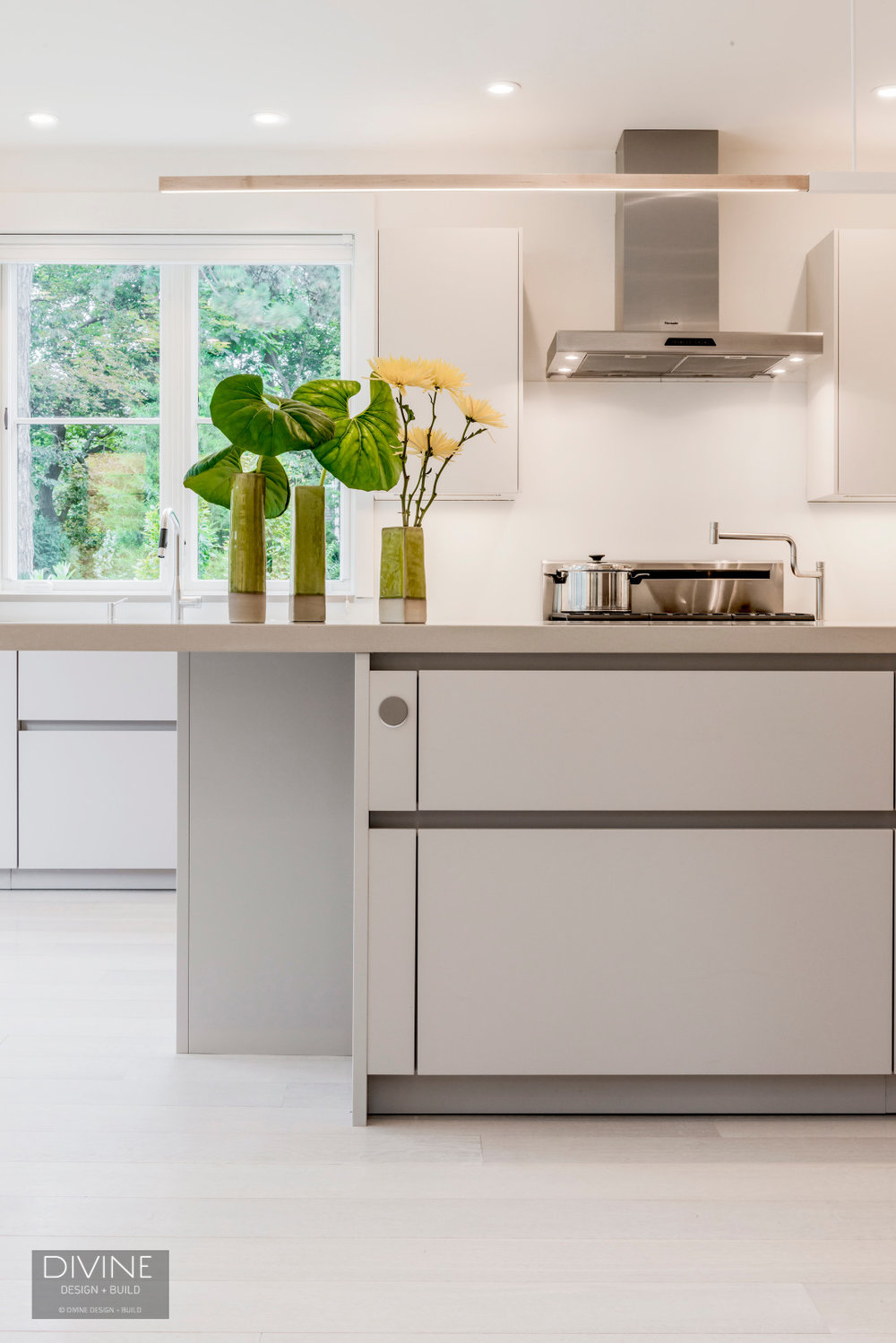 Matt white, modern leicht kitchen cabinets with brushed nickel accessories and walnut accents.