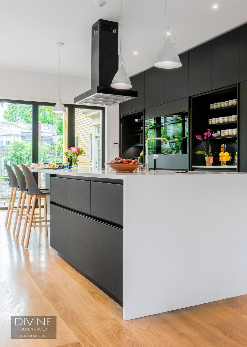 Modern black Leicht kitchen with granite countertops and wolf and sub zero appliances. Black range hood and induction cooktop on the island.