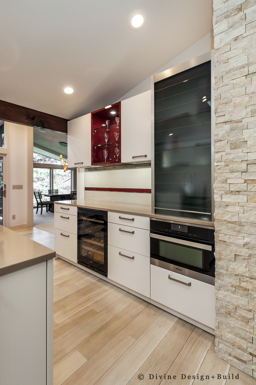 Modern leicht kitchen with mid century modern themes and red detailed accents. Light hardwood floors, and some exposed support beams.