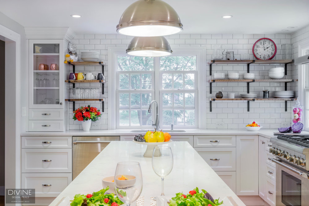Transitional style kitchen with white and grey shaker cabinets. Subway tile backsplash with dark grout. Industrial, open shelving. Dog feeding station.
