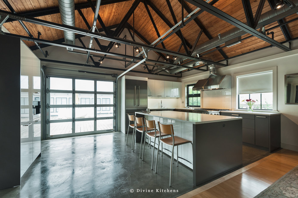 Industrial style loft condo with exposed support beams. Modern leicht kitchen with white and grey cabinets. Paneled appliances.