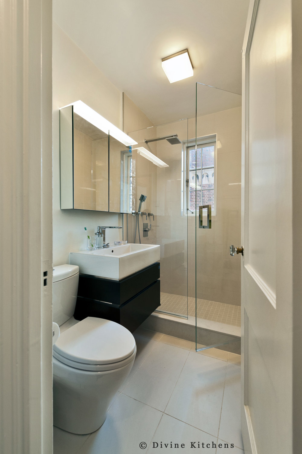 Small guest bathroom with a floating vanity and vessel sink. Step in shower with glass partition.
