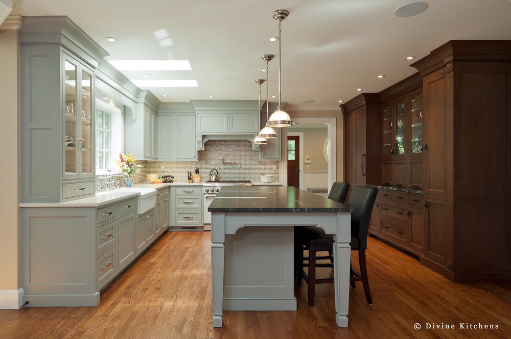 Traditional kitchen inside a historic victorian home. Large windows. Light blue and dark wood shaker cabinets. Mosaic tile backsplash, wolf appliances. Farmhouse sink.