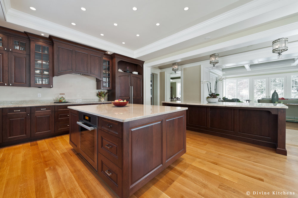 Traditional dark wood cabinets, high ceilings, and two kitchen islands. Marble countertops and luxury appliances.