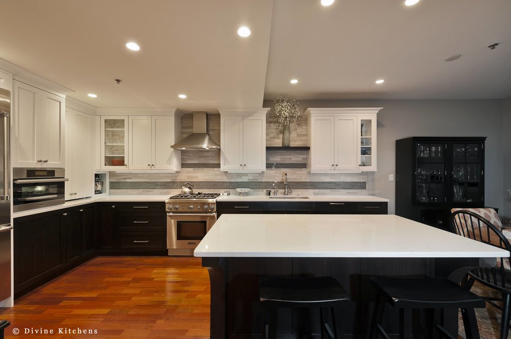 transitional style kitchen inside a converted church. Off-white Shaker cabinets with mosaic tile backsplash.